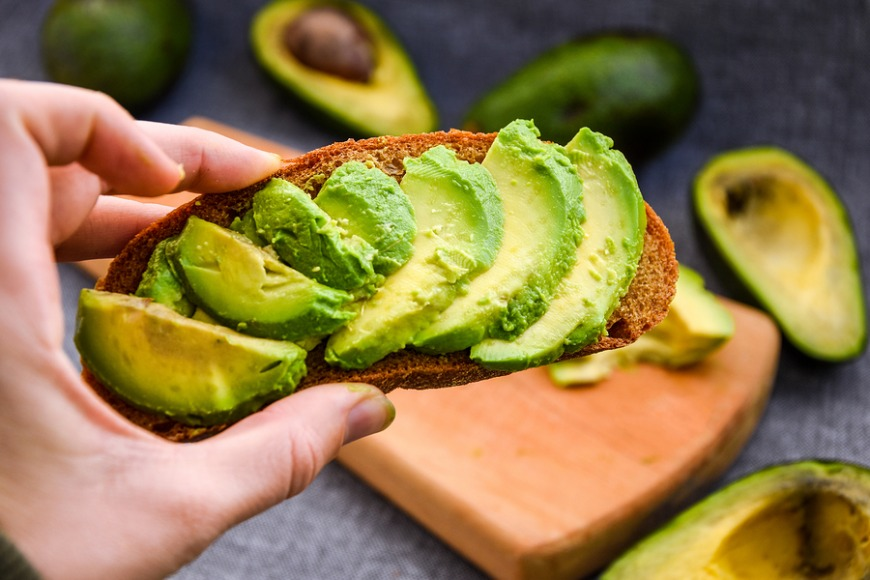 Female hand holding Avocado toast, green organic avocado